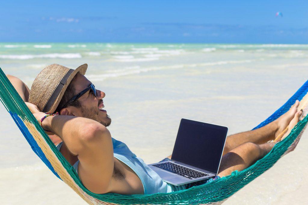 nomada digital en la playa trabajando en modo freelance